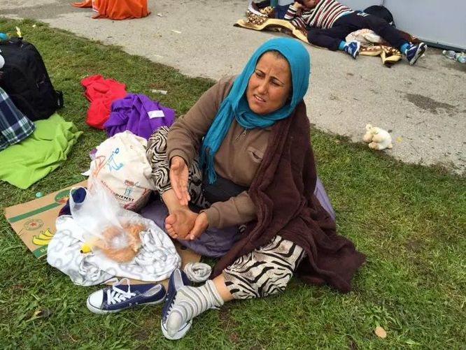 Syrian woman rubs her blistered feet at Austrian train station.