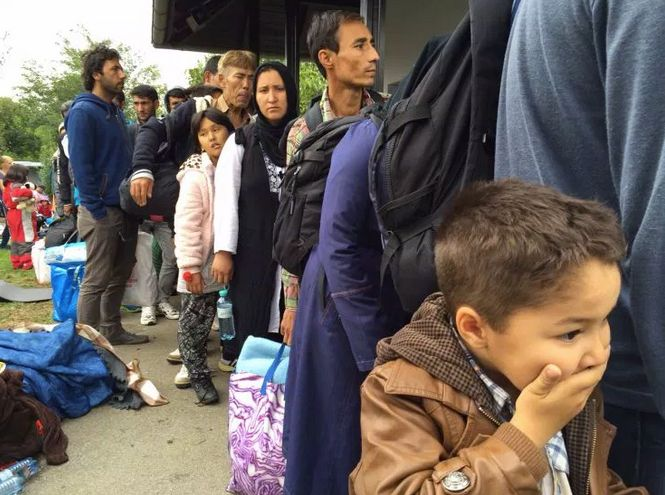 Syrian boy lines up with family to board a train near the Austrian border.