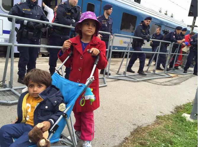 A young Syrian girl pushes her younger brother in a stroller past Austrian police guarding the train.