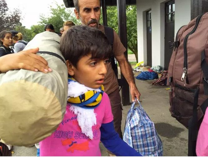 A young Syrian boy and his dad make their way towards the train to Vienna.