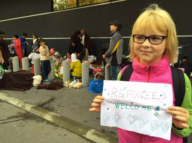 A young Austrian girl welcomes refugees to Vienna.