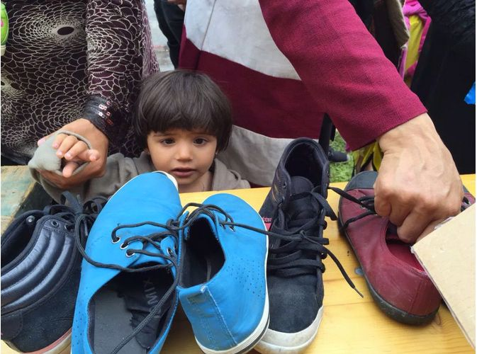 A Syrian girl looks at shoes as the older women grab a pair.
