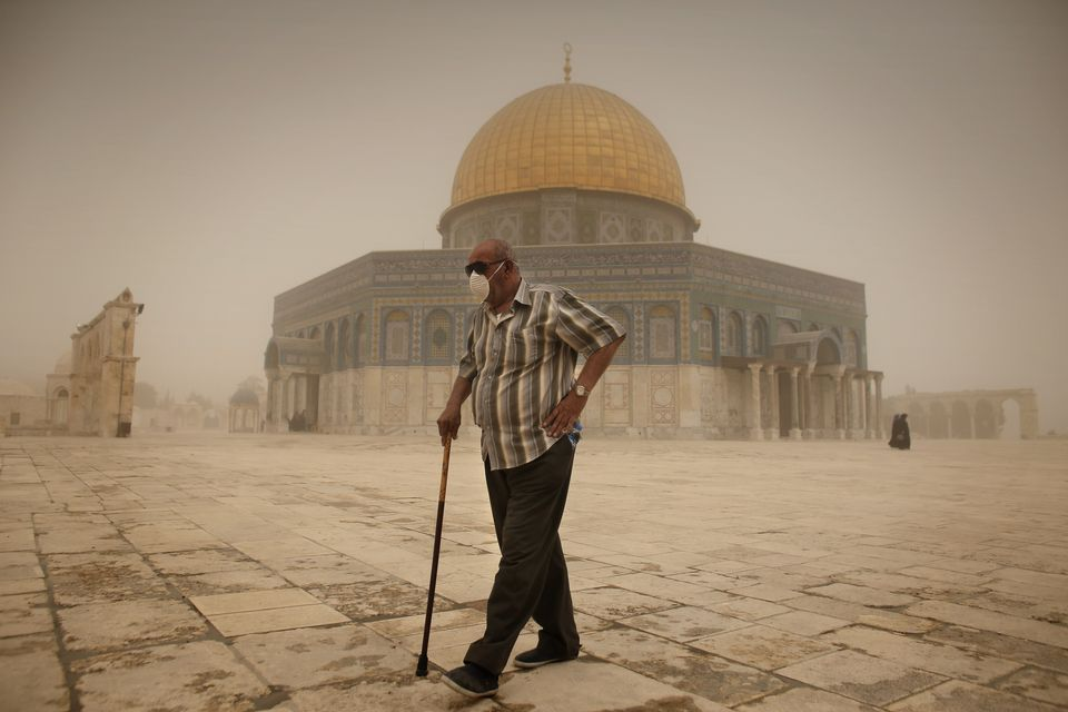 A Palestinian man wears a mask to protect his face from the dust as he walks past the Dome of the Rock...