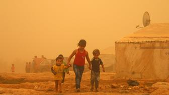 <p>Syrian children walk amid the dust during a sandstorm on Sept. 7, 2015 at a refugee camp on the outskirts of the eastern Lebanese city of Baalbek.</p>
