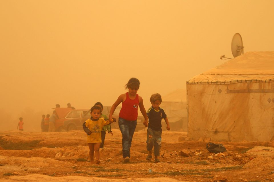 Syrian children walk amid the dust during a sandstorm on Sept. 7, 2015 at a refugee camp on the outskirts...