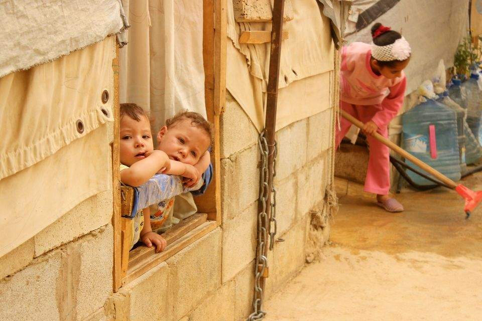 Syrian refugee children look on from a window during a sandstorm at a refugee camp near the Bekaa Valley...