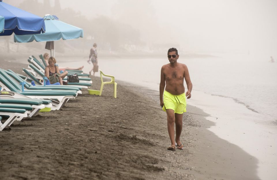 A man walks on the beach in Limassol as a sandstorm hits the east Mediterranean island of Cyprus...