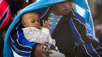 LAMPEDUSA, ITALY - APRIL 23:  A migrant woman and a young child board a ship bound for Sicily on April 23, 2015 in Lampedusa, Italy. It is expected that EU leaders in Brussels are to agree later that only 5,000 resettlement places across Europe are to be offered to refugees under a new emergency summit crisis package. Hundreds of migrants continue to arrive in Lampedusa from North Africa taking advantage of calm seas. Hundreds of migrants are believed to have perished over the last week as they attempted to cross the Mediterranean from Libya to Italy in order to seek refuge.  (Photo by Dan Kitwood/Getty Images)