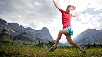 Runner skips into air above mountain trail