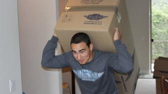 Guy moving a wardrobe box on this back, meathead moving a box