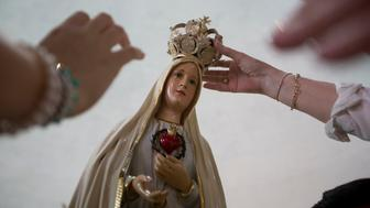 Women place a crown on an image of Our Lady of Fatima during a celebration in her honor at the Metropolitan Cathedral in Managua, Nicaragua, Wednesday, May 13, 2015. Our Lady of Fatima is the title given to the apparition of the Virgin Mary to three shepherd children in Fatima, Portugal in 1917. (AP Photo/Esteban Felix)