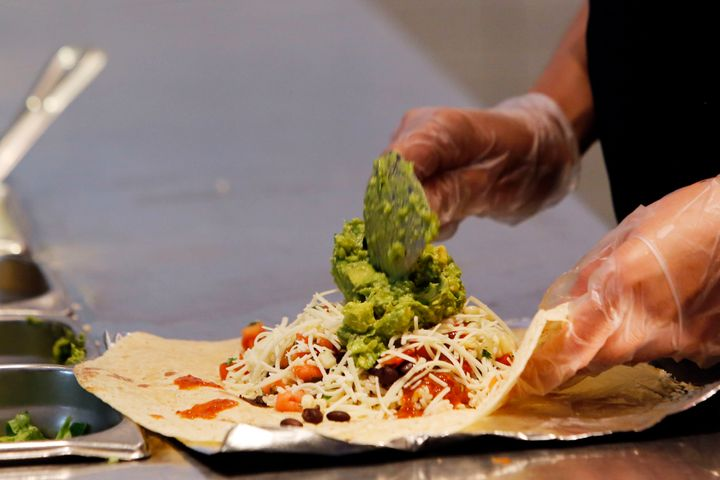 A Chipotle worker, who's presumably not sick, prepares a burrito.