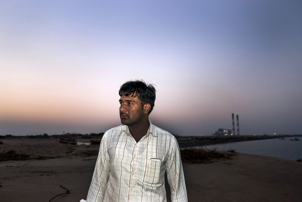 <span>Gajendrasinh Jadeja, an elected village chief in western India, stands in front of a coal-burning power plant financed
