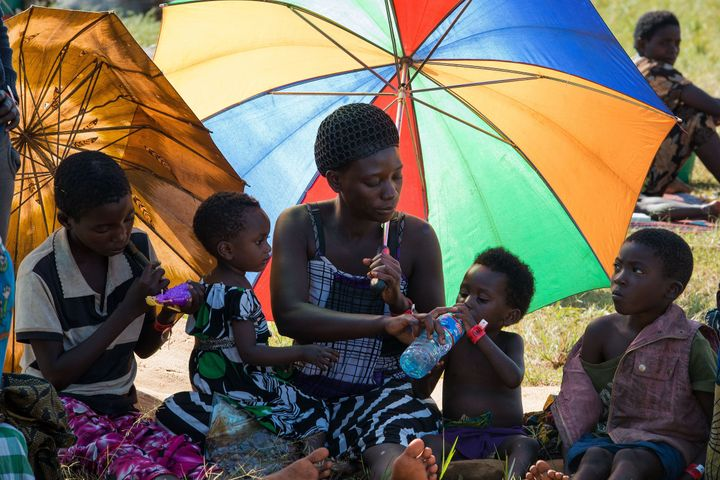 <span>A family of Burundian refugees rests in the shade of their umbrellas at the Lake Tanganyika Stadium in Kigoma, on May 2