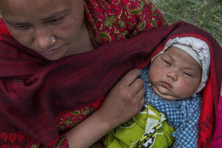 <span>&nbsp;A mother holds her child in an evacuation area set up by the authorities in Tundhikel park on April 27, 2015 in K