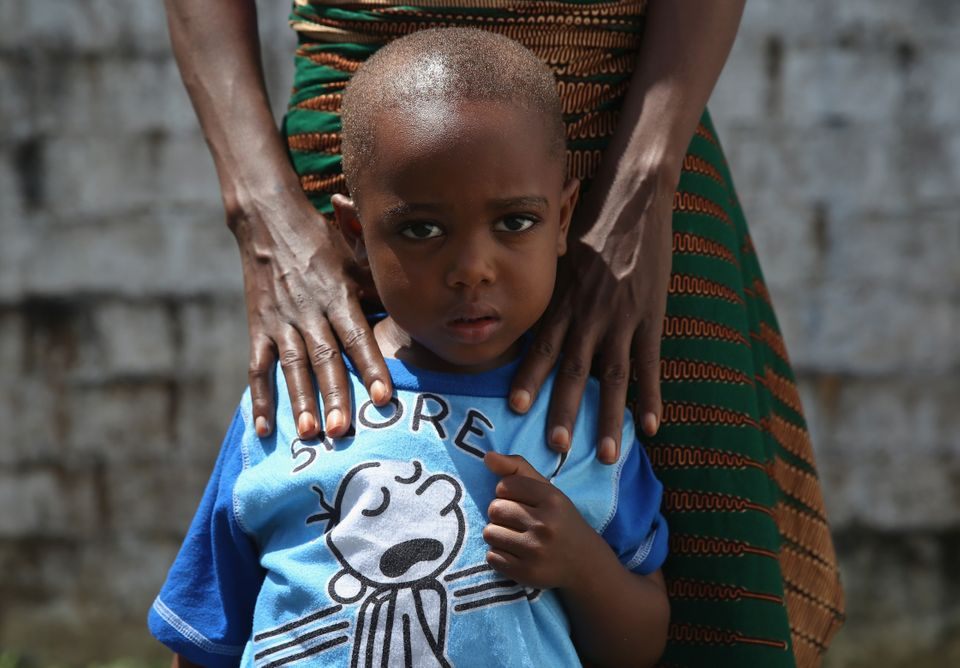 Ebola survivor James Mulbah, 2, stands with his mother, Tamah Mulbah, 28, who also recovered from Ebola in the low-risk secti
