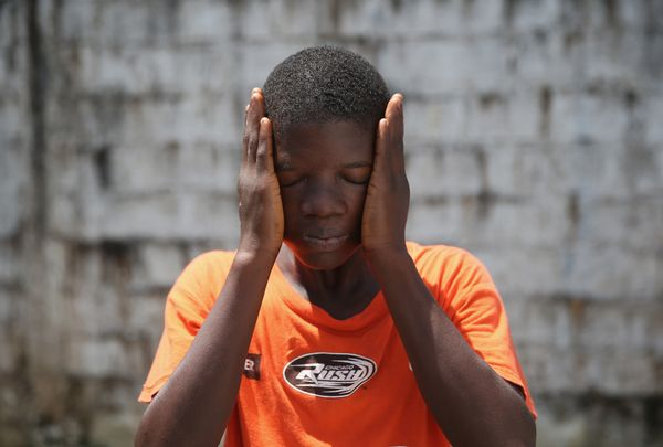 Ebola survivor Jeremra Cooper, 16, wipes his face from the heat while in the low-risk section of the Doctors Without Borders