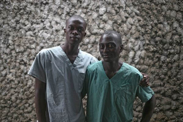 Ebola survivors Zaizay Mulbah, 34, and Mark Jerry, 30, right, stand together before their shifts as nurse's assistants at the