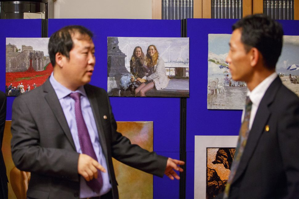 An art exhibition at the North Korean embassy in London. Center, a painting of two Western girls on a London street