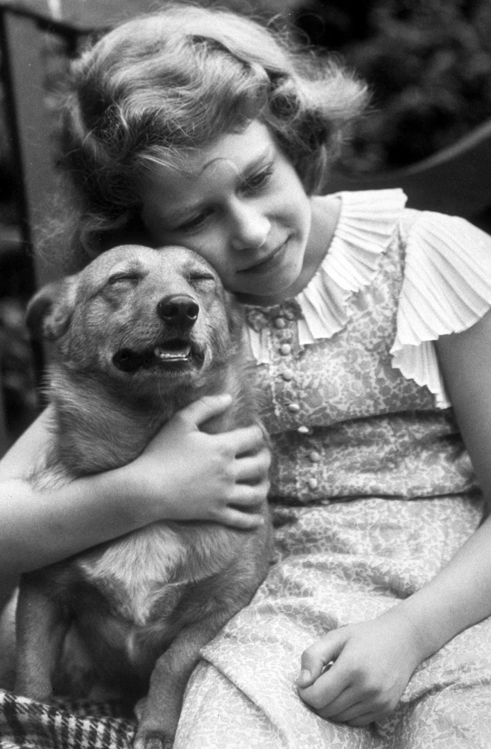 July 1936:  Princess Elizabeth hugging a corgi dog.  (Photo by Lisa Sheridan/Studio Lisa/Getty Images)