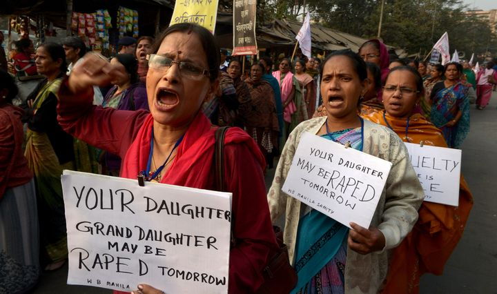 <span>Women's rights&nbsp;activists carry posters as they shout slogans during a protest march against the gangrape and murde