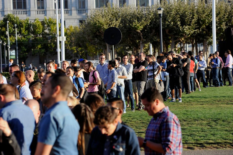 Attendees line up in front of the Bill Graham Civic Auditorium before the start of the Apple event in San Francisco, Californ