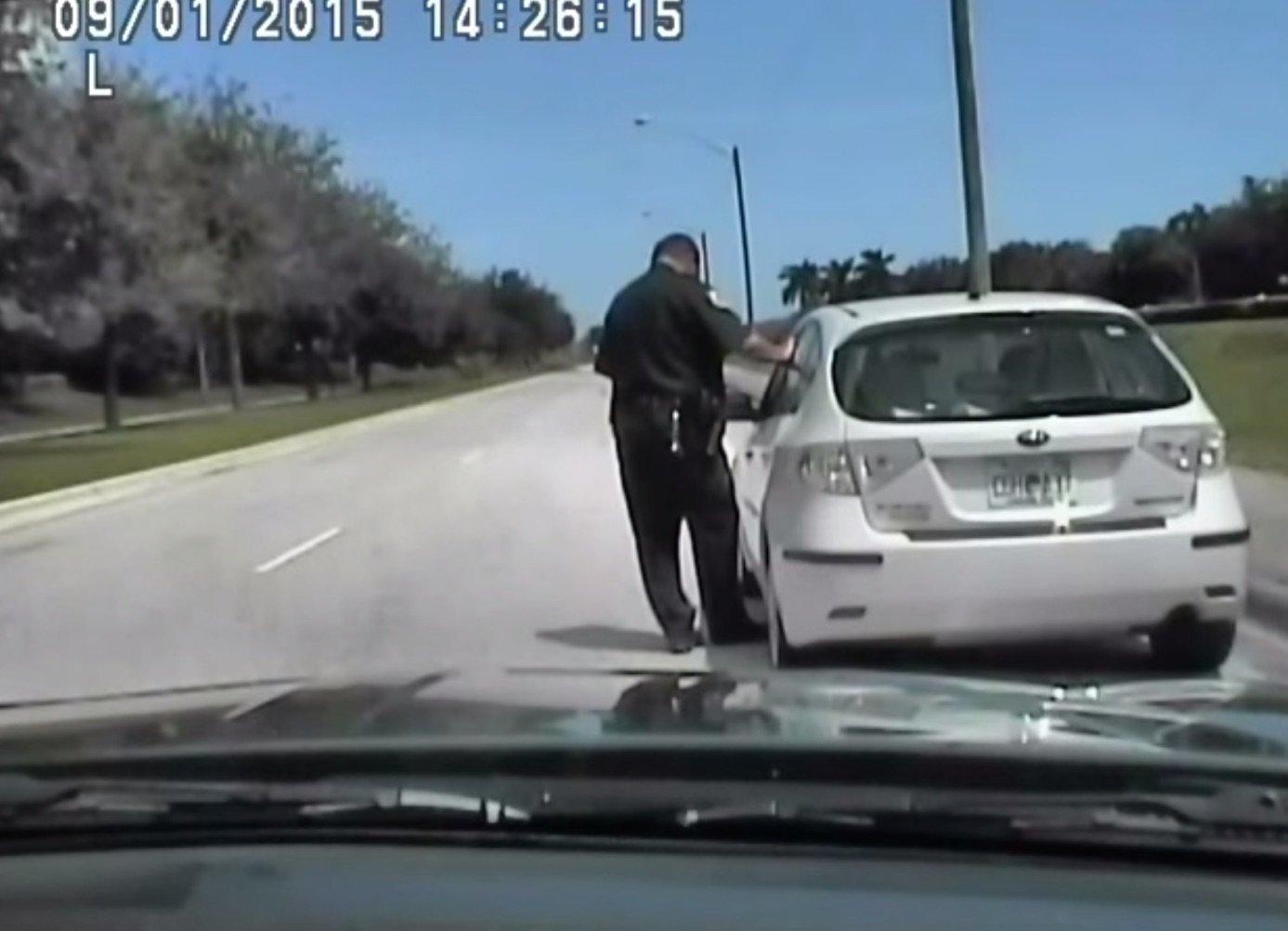 A cop tickets a driver.
