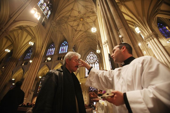 Seminarian Richard Marrano (R) distributes ahes to a worshiper during Ash Wednesday services at Saint Patrick's Cathedral on