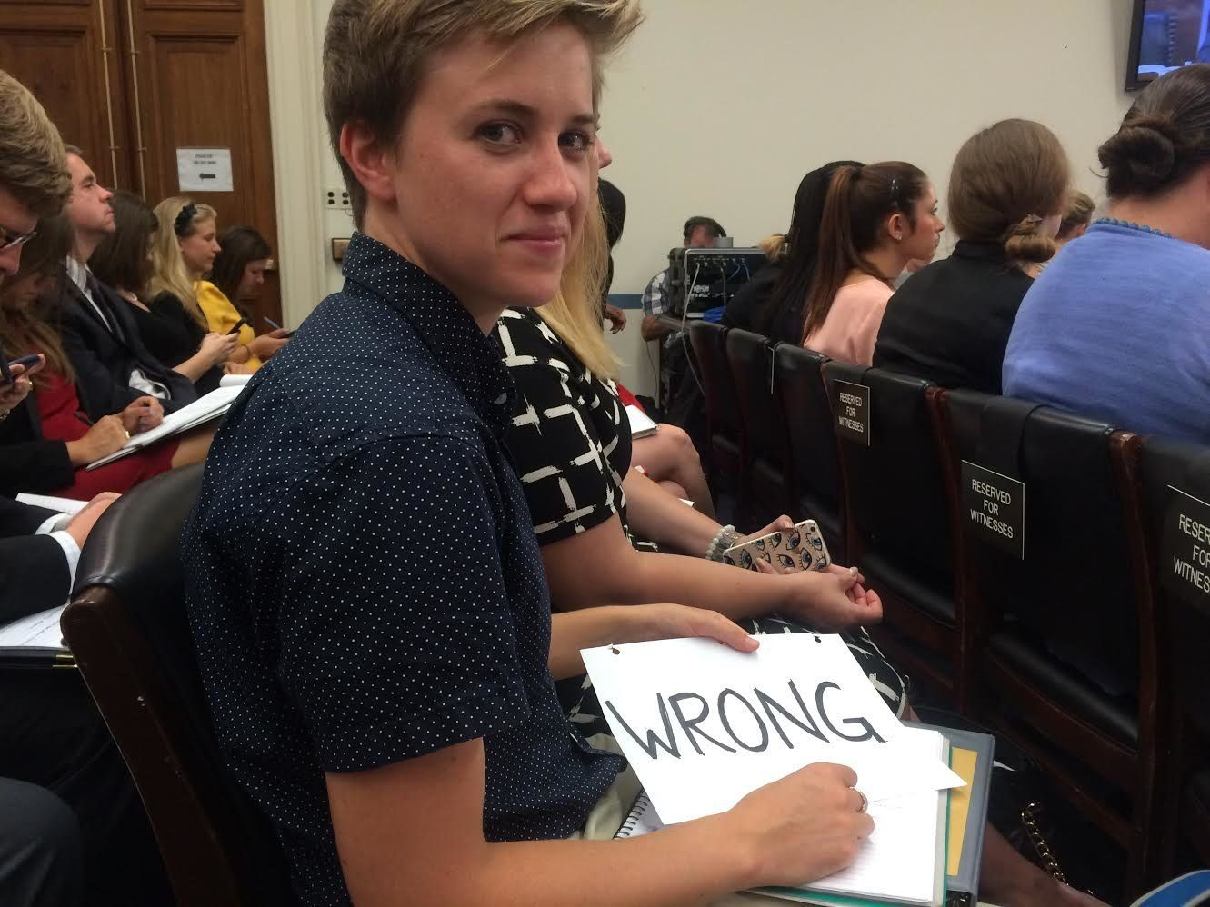 A Stanford University student at a House Education and the Workforce Committee hearing holds a sign to oppose some witnesses'