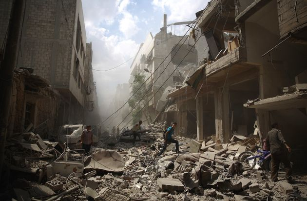 "<span class='image-component__caption' itemprop=""caption"">Syrians walk through the rubble caused by an alleged government airstrike in Douma, Syria.</span>"
