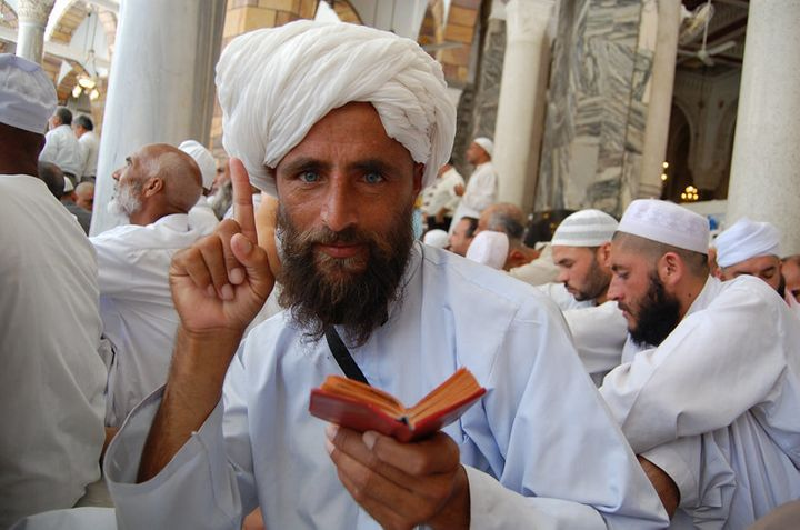 "An Afghan ""Hajji"" (pilgrim) raises his index finger to denote a central precept of Islam, while holding a Quran i"