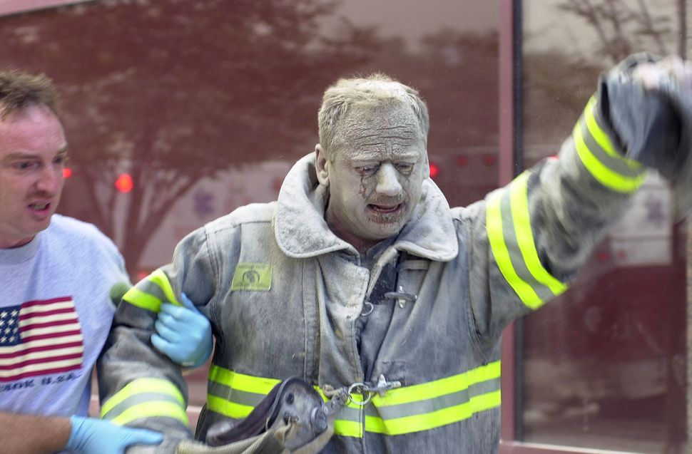 """<span style=""""color: #222222;"""">A firefighter is covered with ash after the attacks.&nbsp;</span>"""