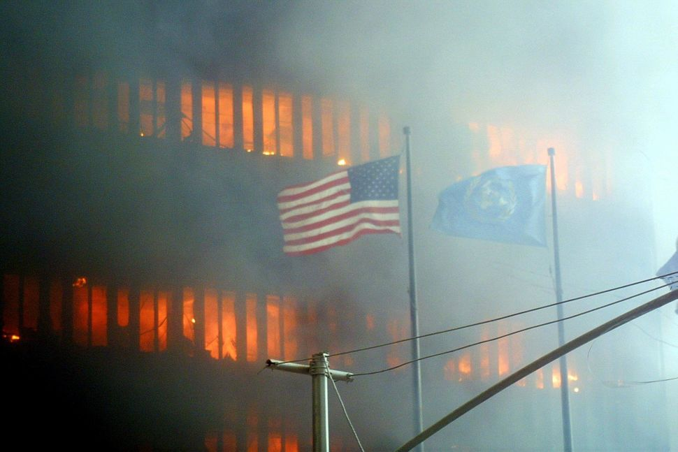 "<span style=""color: #222222;"">An American flag flies in the foreground as one of the World Trade Center towers burns in the b"