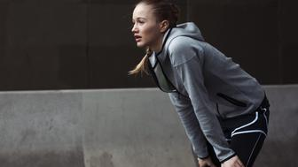 a blond sporty woman is resting after sports, hands on her knees, breathing out, in an urban environment