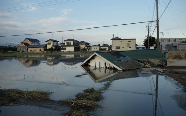 A collapsed house lies in a flooded paddy field in Joso, Japan, on Sept. 11, 2015.