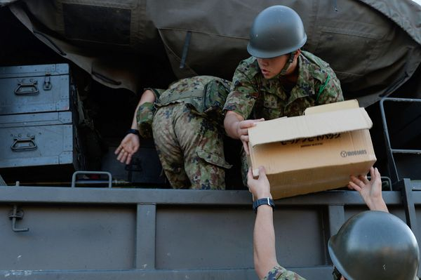 Members of Japan's Self-Defense Force hand out relief goods in Joso, Japan, on Sept. 11, 2015.