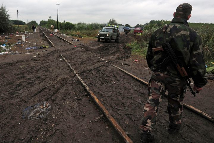 Soldiers of the Hungarian army and police officers stand at the rail tracks at the Hungarian-Serbian border near Roszke on Se