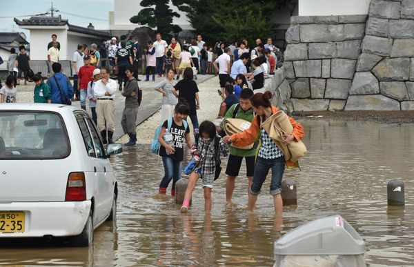 Residents walk on a flooded street in Joso, Japan, on Sept. 11, 2015.