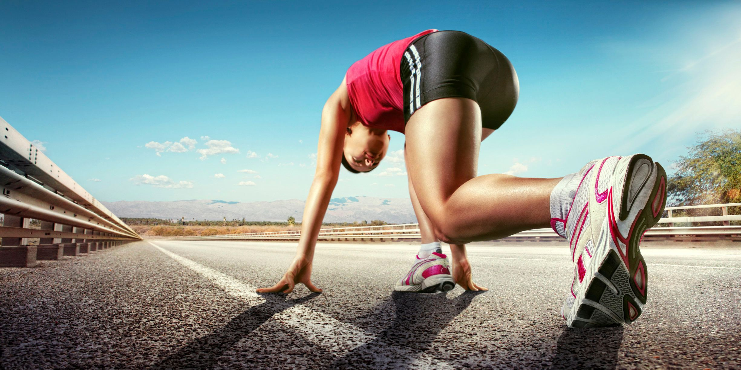 low angle view of female runner running down road wearing trainers