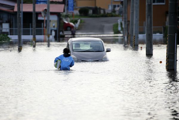 A man walks through floodwaters in Osaki, Miyagi prefecture, Japan, on Sept. 11, 2015.