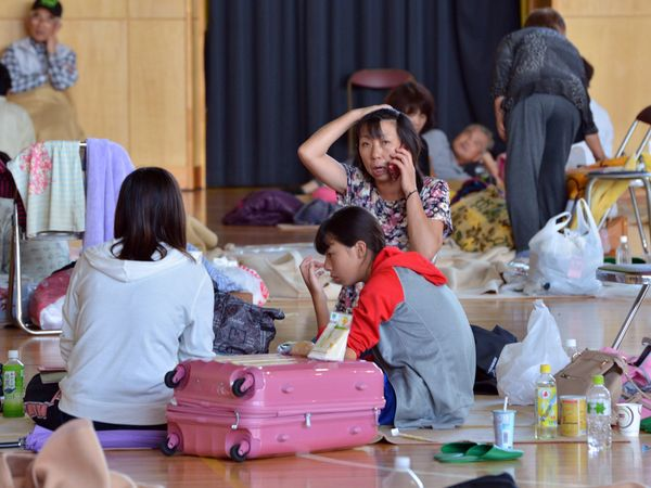 People rest and talk on the phone at an evacuation shelter in Tsukubamirai, Ibaraki prefecture on Sept. 11, 2015.