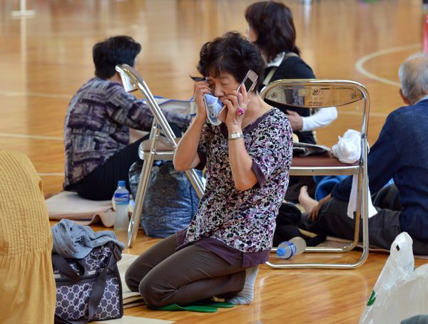 A woman speaks on her mobile phone at an evacuation center in Tsukubamirai, Ibaraki prefecture, on Sept.11, 2015.