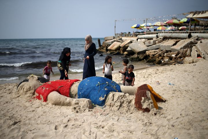 Palestinian girls put flowers on a sand sculpture on a Gaza City beach depicting Syrian refugee Aylan Kurdi, a 3-year-ol