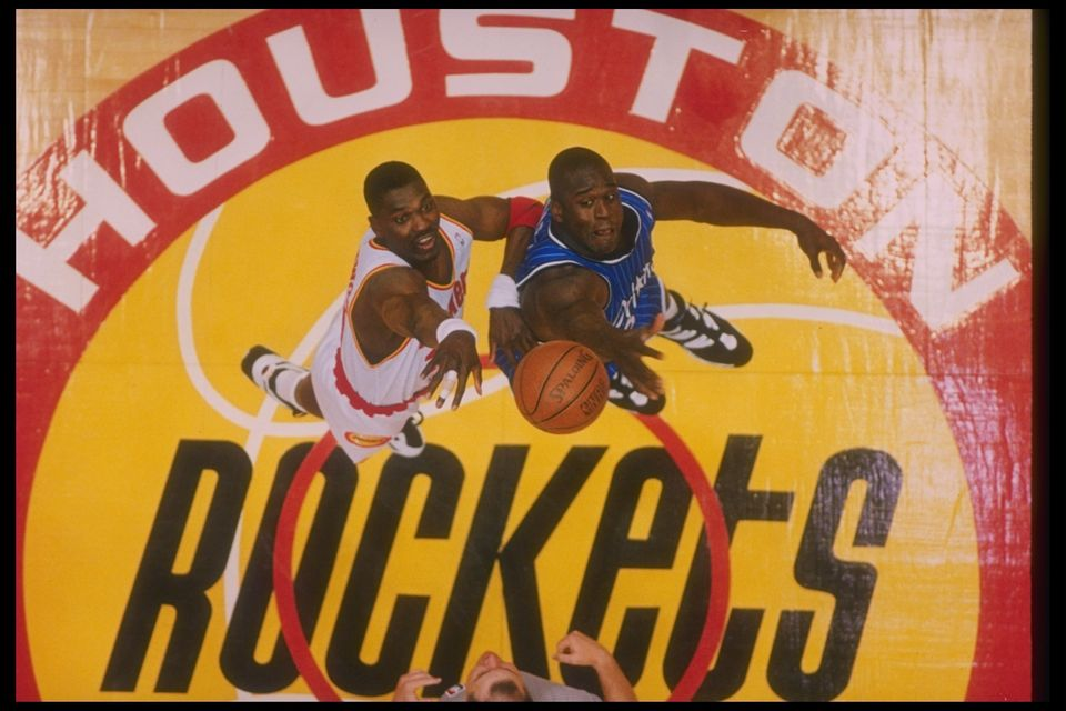 Center Hakeem Olajuwon of the Houston Rockets and Orlando Magic center Shaquille O'Neal go up for the ball during a Finals ga