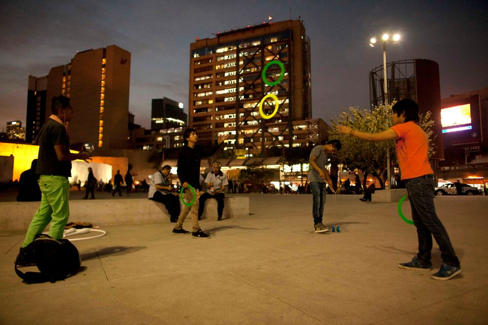 In this photo taken on Dec. 13, 2012, young men play catch with flying rings at the Glorieta de Insurgentes roundabout and me