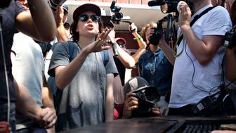 Actress Ellen Page questions Senator Ted Cruz, a Republican from Texas and 2016 presidential candidate, not pictured, on gay-rights issues as Cruz works the grill at the Iowa Pork Producers tent during the Iowa State Fair in Des Moines, Iowa, U.S., on Friday, Aug. 21, 2015. A day after Jimmy Carter appeared on national television to talk about the cancer that's ravaging his body, Cruz criticized the former president's administration in a speech in Iowa. Photographer: Daniel Acker/Bloomberg via Getty Images