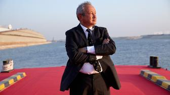 Egyptian billionaire Naguib Sawiris poses for a photograph on a floating pontoon in front of the New Suez Canal, operated by the Suez Canal Authority, in Ismailia, Egypt, on Thursday, Aug. 6, 2015. The expansion will meet future demand, with traffic expected to double to 97 vessels a day by 2023, said Mohab Mameesh, head of the Suez Canal Authority. Photographer: Shawn Baldwin/Bloomberg via Getty Images