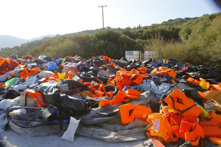 A huge pile of life jackets, other inflatable devices and inflatable rubber dinghies that were used by the refugees com
