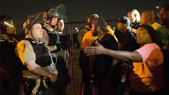FERGUSON, MO - AUGUST 10:  Demonstrators, marking the one-year anniversary of the shooting of Michael Brown, confront police during a protest along West Florrisant Street on August 10, 2015 in Ferguson, Missouri. Mare than 100 people were arrested today during protests in Ferguson and the St. Louis area. Brown was shot and killed by a Ferguson police officer on August 9, 2014. His death sparked months of sometimes violent protests in Ferguson and drew nationwide focus on police treatment of black suspects.  (Photo by Scott Olson/Getty Images)