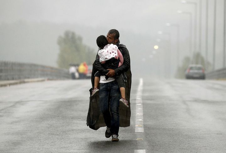 A Syrian refugee kisses his daughter as he walks through a rainstorm towards Greece's border with Macedonia, near the Greek v